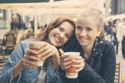 Two young women drinking coffee and smiling after having their teeth whitened - Alder Dental, Vancouver WA